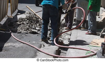 Road worker use jackhammer - A portable jackhammer being...