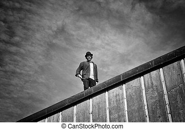 Looking down - Young man looking down from roof, dramatic...