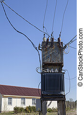 Electricity Power Distribution Transformer near the residential rural home.