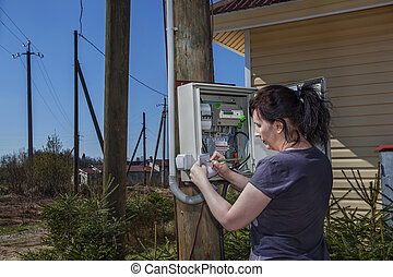 Woman takes readings of the electric meter, outdoors.