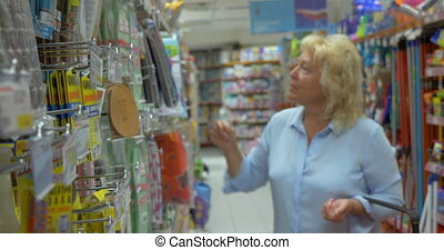 Senior woman in the hypermarket - Senior blond woman...