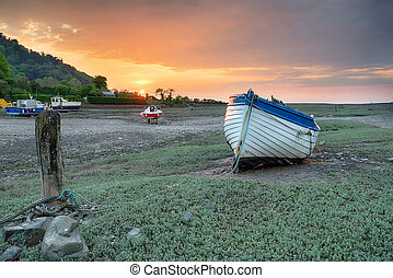 An old wooden fishing boat at low tide on Porlock Weir on...