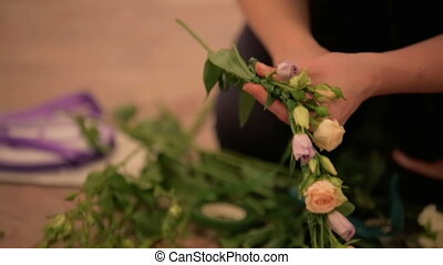 Bridesmaid weaves a wedding wreath of pink roses.