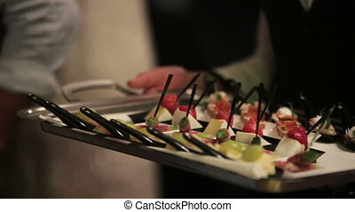 Close-up of waiter holding a tray with sweet desserts with berries