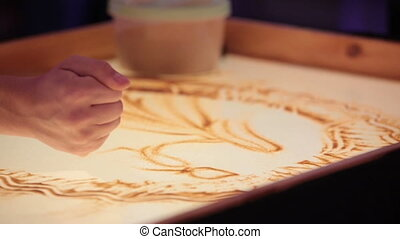 Sand animation. Girl draw pictures with sand by the hand.