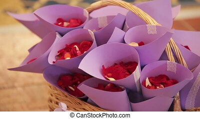 Wedding ?eremony. On the wooden background is a wicker basket, there are envelopes with rose petals for wedding celebration