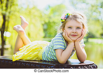 cute stylish little girl posing at park