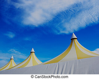 Upper part of a big colorful plastic tent. Blue sky and...