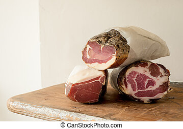 Logs of Cured Meat - Logs of cured or preserved meat on a...