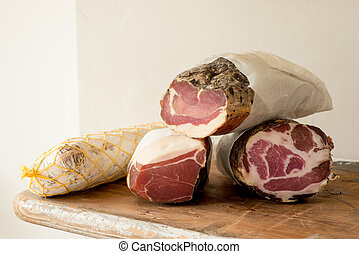 Logs of Cured Meat - Logs of deli meat on a wooden counter