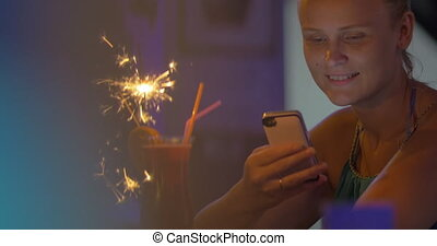 Woman with Smartphone in Bar - Young smiling woman is...