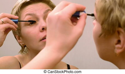 Pretty woman applying eyelashes mascara makeup - Pretty...