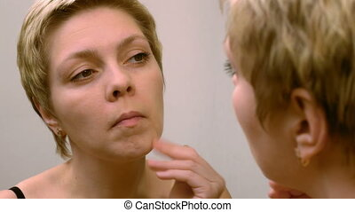 Woman applies makeup concealer foundation cream - Beautiful...