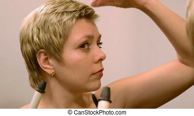 Short hair woman curls her hair with curling iron - Pretty...
