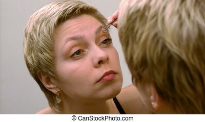 Woman plucks and pulls her eyebrows out at mirror