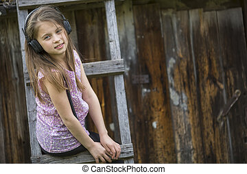 Cute little girl with headphones, portrait outdoors.