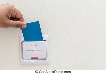 Hand holding blue hotel key card insert to electric switch -...