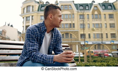 young man drinking coffee in the city