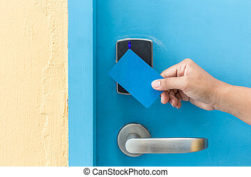Hand holding blue hotel keycard in front of electric door -...