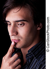 Portrait of a handsome young man thinking, on black background. Studio shot