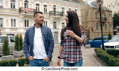 Young attractive couple walking together in the city while on vacation during a sunny day.