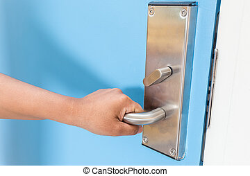Hand holding on stainless steel door handle in hotel - Close...