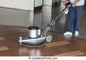 Woman cleaning the floor with polishing machine