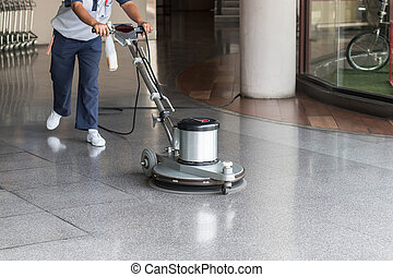 Woman cleaning the floor with polishing machine - Woman...