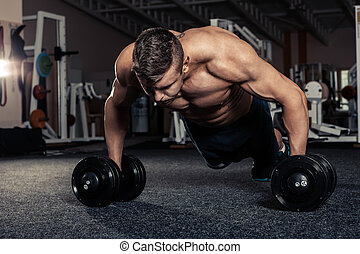 Gym man push-up strength pushup exercise with dumbbell -...