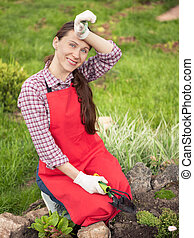 Young woman planting flowers in garden Gardening
