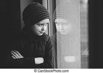 Confident 7 year old boy looks out the window - B and W -...