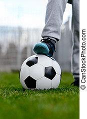 Feet of little boy on ball on football field, outdoors Child...