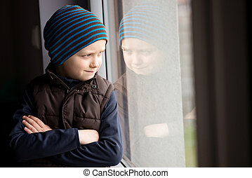 Confident 7 year old boy looks out the window He is wearing...