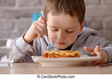 7 years old boy eating lasagne in dining room Wears grey...