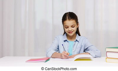 school girl hand writing math task to notepad