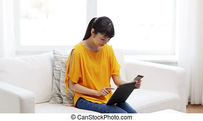 happy asian woman with tablet pc and credit card - people,...