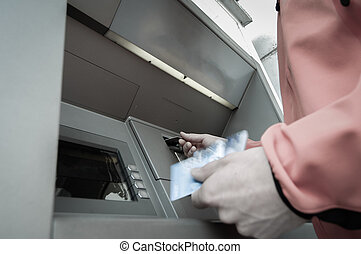 Man at ATM machine with stash of credit and debit cards -...