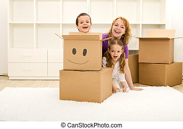 Happy kids and woman having fun in their new home