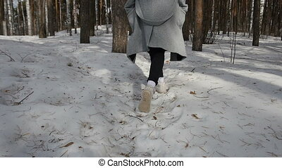 Girl walking in winter forest