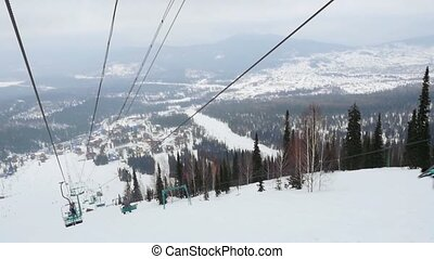 Ski lift chairs on snowy foggy winter day in slowmotion....
