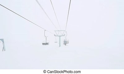 Ski lift chairs on foggy milk winter day in slowmotion...