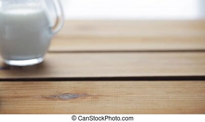 sugar falling into cup of coffee on wooden table - unhealthy...
