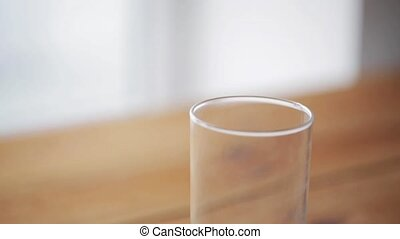 orange juice pouring into glass on wooden table