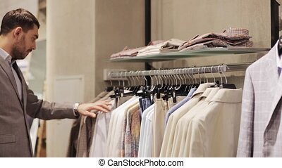 happy young man choosing clothes in clothing store - sale,...