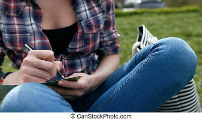 Young woman in in checkered shirt and blue jeans writing in...