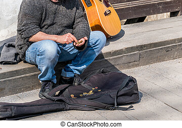 busker counts its receipts - a street musician counts its...