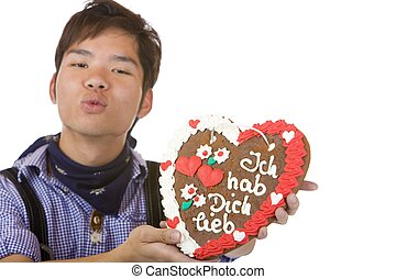 Chinese holds an Oktoberfest gingerbread heart in camera