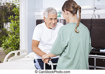 Senior Man Being Assisted By Female Nurse In Using Walker -...