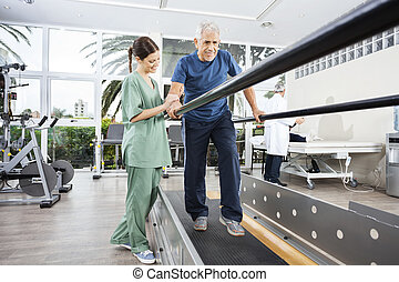 Physiotherapist Standing By Smiling Patient Walking Between...