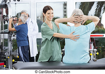 Female Nurse Assisting Senior Woman In Back Exercise -...